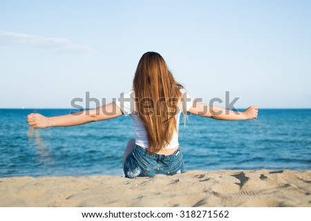 Portrait of a young hipster girl with luxurious long hair sitting with open arms in front of beautiful calm sea and blue sky enjoying landscape, woman relaxing on the beach in feeling of freedom - stock photo