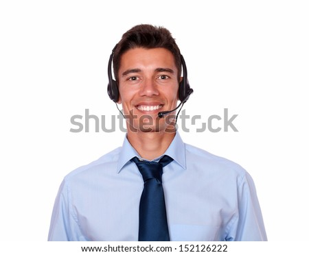 Portrait of a young hispanic businessman speaking on headphones with microphone while standing against white background