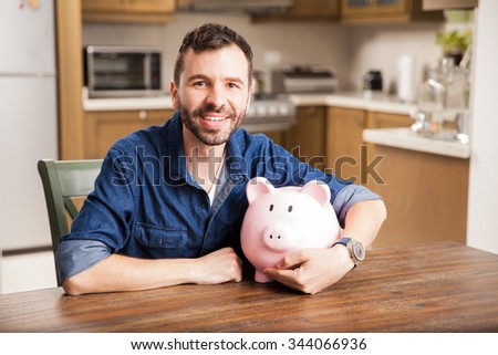 Portrait of a young Hispanic man with a beard holding a piggy bank and smiling at home