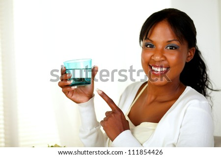 Portrait of a young lady pointing to a fresh water glass while smiling friendly on a light background - stock photo