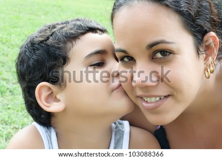 Portrait of a young latin woman and her son kissing - stock photo