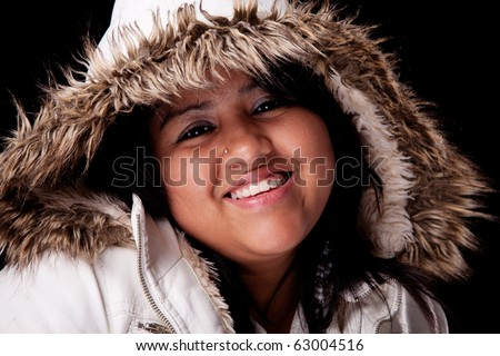 Portrait of a young latin woman with a furry hood , in autumn/winter clothes, isolated on black. Studio shot - stock photo