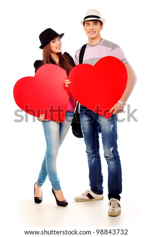 Portrait of a young loving couple holding big hearts. Isolated over white. - stock photo