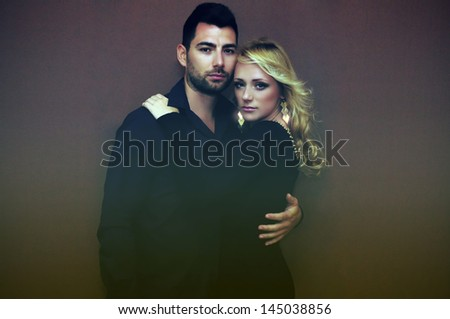 Portrait of a young loving couple in dim light. - stock photo