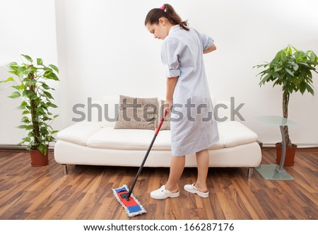 Portrait Of A Young Maid In Uniform Cleaning Floor With Mop - stock photo