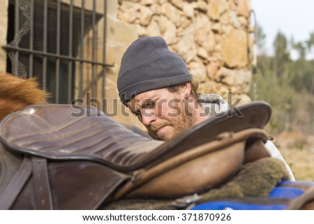 Portrait of a young male adjusting the saddle on his horse - stock photo