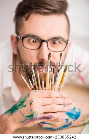 Portrait of a young male artist with many brushes for painting is looking at the camera through them. - stock photo
