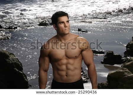 Portrait of a young male bodybuilder against background of sparkling water on beach - stock photo