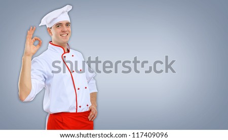 Portrait of a young male cook in red apron against colour background - stock photo