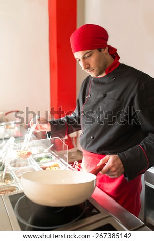 Portrait of a young male cook preparing a meal in the wok pan - stock photo