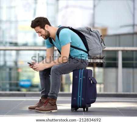 Portrait of a young male traveler sitting on suitcase and sending text message  - stock photo