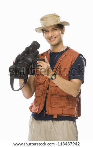 Portrait of a young male videographer holding a videography camera