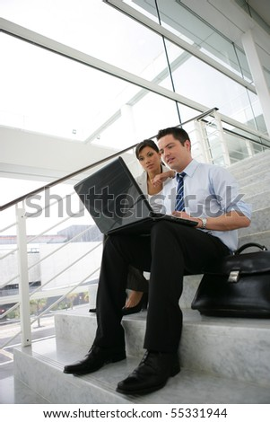 Portrait of a young man and a young woman in suit in front of a laptop computer sitting on stairs - stock photo