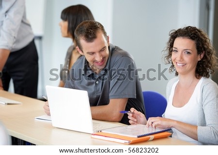 Portrait of a young man and a young woman smiling sitting at a desk in front of a laptop computer - stock photo
