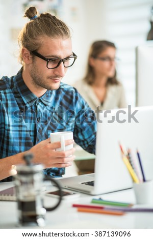 portrait of a young man at his computer, a mug in his hand, at the background his female colleague works at his desk. Shot with flare - stock photo