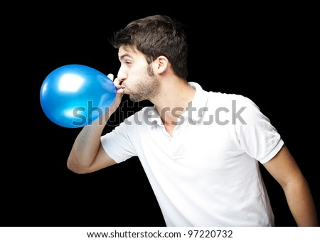 portrait of a young man blowing up a blue balloon against a black background - stock photo
