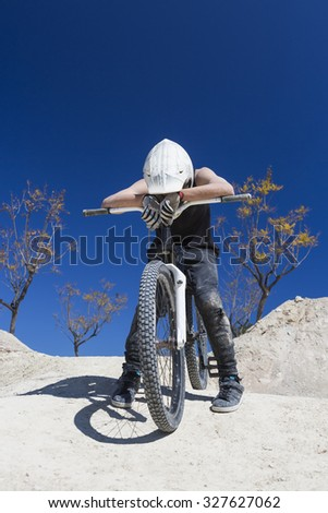 portrait of a young man BMX biker exhausted sitting on his bike after a BMX session in the mountain - focus on the face - stock photo