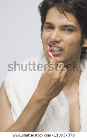 Portrait of a young man brushing his teeth