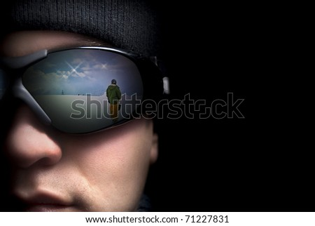 Portrait of a young man close up. In the glasses reflection the mountains and snowboarders - stock photo