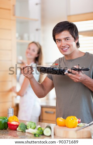 Portrait of a young man cooking while his wife is washing the dishes in their kitchen - stock photo