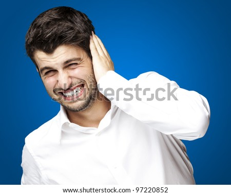 portrait of a young man covering his ear against a blue background - stock photo