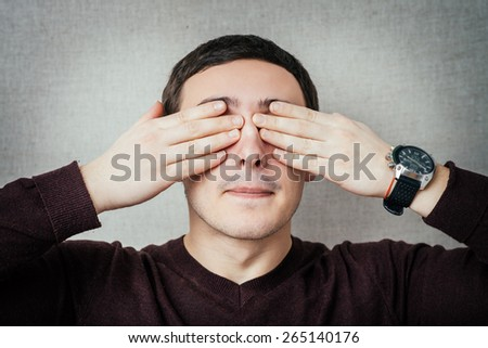 Portrait of a young man covering his eyes with hands - stock photo