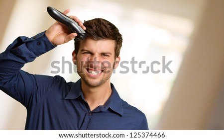 Portrait Of A Young Man Cutting His Hair, Indoors - stock photo