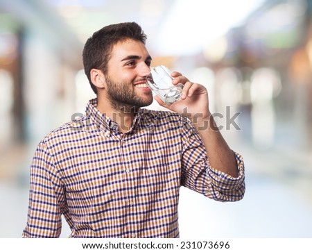 portrait of a young man drinking a water glass - stock photo