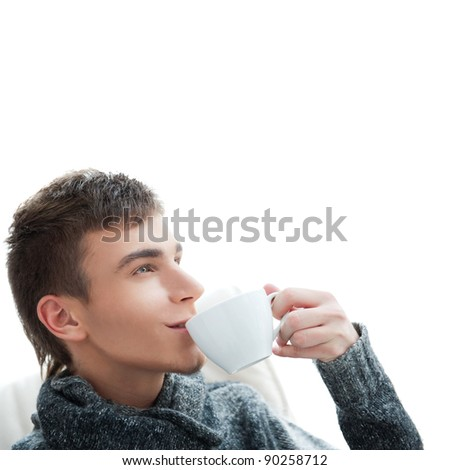 Portrait of a young man drinking coffee and looking away,  lots of copyspace