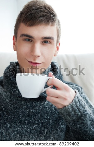Portrait of a young man drinking coffee while sitting on armchair at home - Indoor