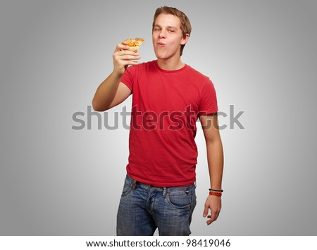 portrait of a young man eating a piece of pizza against a grey background
