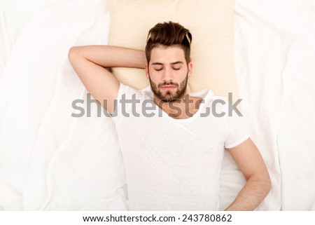 Portrait of a young man from above sleeping in a white bed.  - stock photo