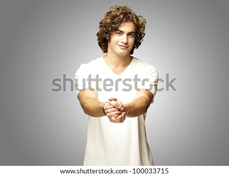 portrait of a young man gesturing a contract over a grey background