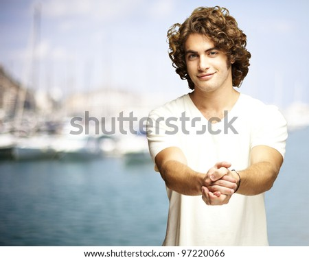 portrait of a young man gesturing contract against a harbor background - stock photo