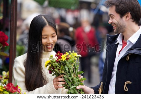 Portrait of a young man giving flowers to beautiful woman - stock photo