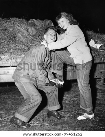 Portrait of a young man helping a young woman board a trailer - stock photo