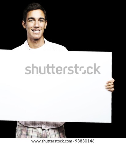 portrait of a young man holding a big white sign against a black background - stock photo