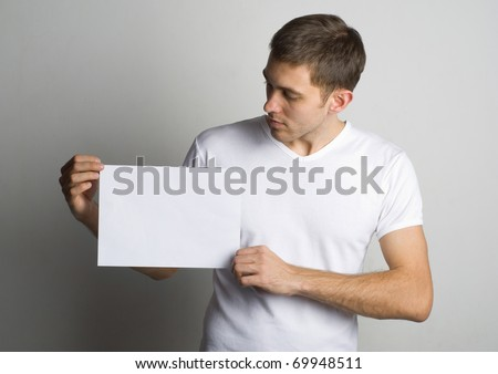 Portrait of a young man holding a blank board for text near the wall - stock photo