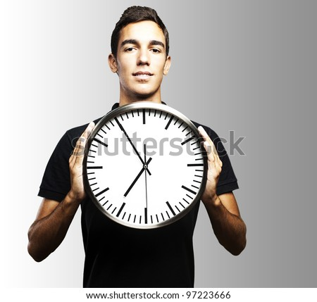 portrait of a young man holding a clock with his hands over a grey background - stock photo