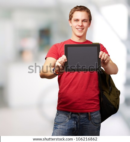 portrait of a young man holding a digital tablet indoor