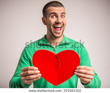 Portrait of a young man holding a large paper heart to his girlfriend - stock photo