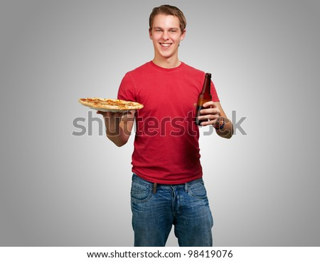 portrait of a young man holding a pizza and a beer over a grey background - stock photo