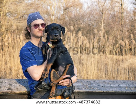 Portrait of a young man holding a rottweiler puppy outdoors