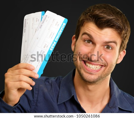 Portrait Of A Young Man Holding Boarding Pass On Black Background