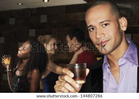 Portrait of a young man holding drink with people dancing behind in the bar - stock photo