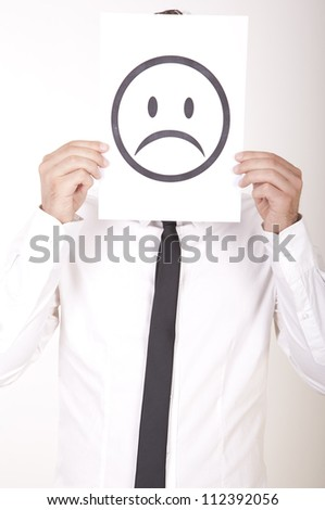 Portrait of a young man holding sad smiley face. - stock photo