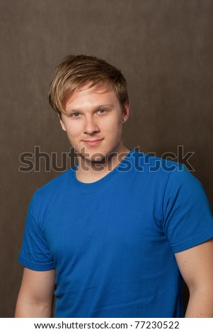 portrait of a young man in a blue t-shirt on grey background - stock photo
