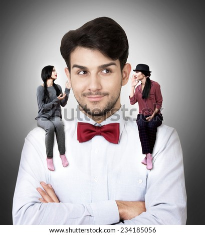 Portrait of a young man in a bow tie with two talking women sitting on his shoulders - stock photo