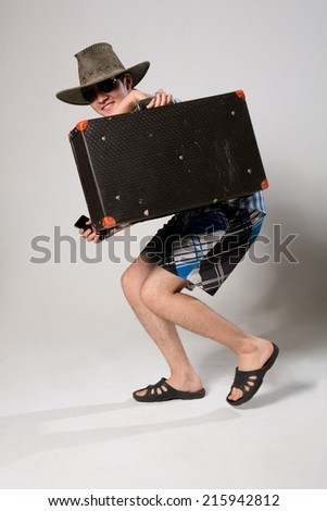 Portrait of a young man in a full-length coming from the suitcase. On a light background in the studio with a phone in his hand - stock photo