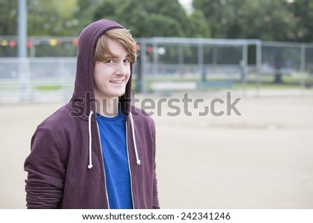 portrait of a young man in a hoodie on a sports field - stock photo